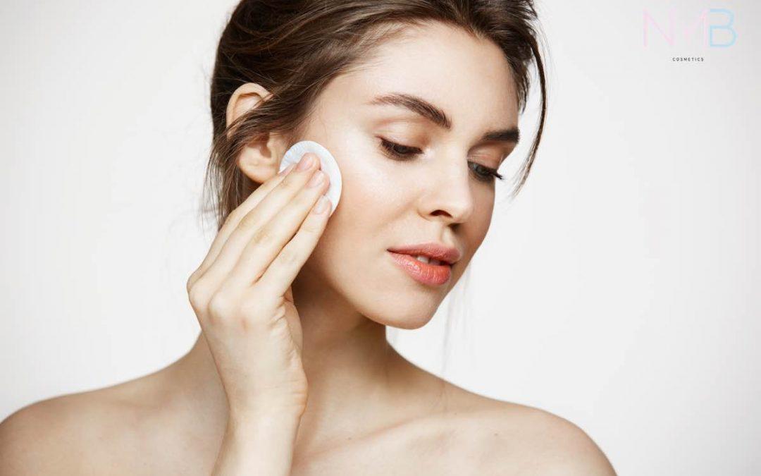 Mujer limpiando la piel de su cara con un disco desmaquillador