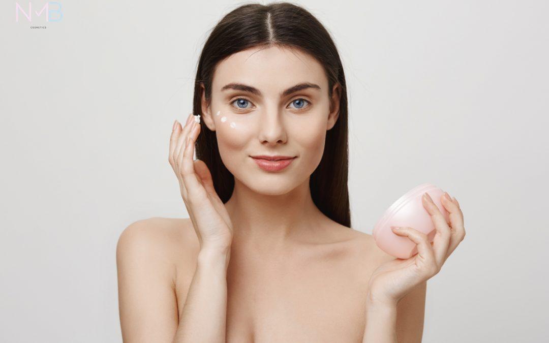Mujer aplicando crema en su rostro.